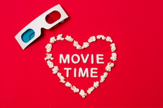 Heure du film écrit en forme de coeur avec des lunettes 3d sur fond rouge Photo gratuit