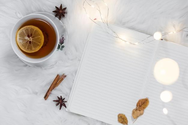 L'heure du thé sur un plaid en fourrure blanche avec un cahier Photo gratuit