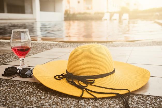 Heure d'été. chapeau, lunettes de soleil et verre de vin au bord d'une piscine Photo Premium
