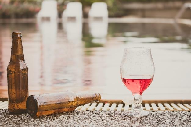 L'heure de la fête. bouteille de bière et de verre de vin à côté d'une piscine Photo Premium