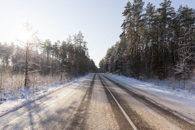 L'heure D'hiver Sur Une Route étroite Dans La Forêt, La Route Est Recouverte De Neige Après Les Chutes De Neige, Temps Glacial Sur Une Route Glissante Et Dangereuse Pour Le Transport Photo Premium