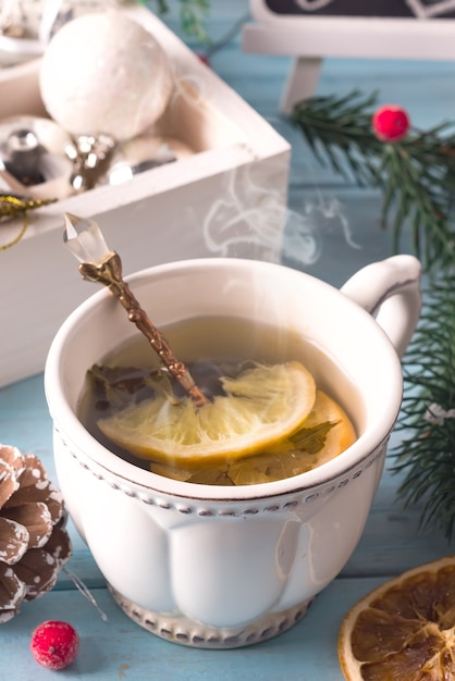 Heure d'hiver. tasse de thé chaud au citron, jouets de noël et foulard en laine. fermer Photo Premium