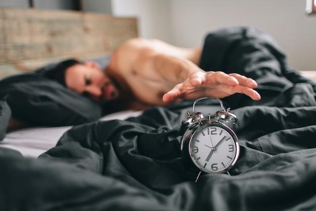 Heure De Se Réveiller. Homme Fatigué Dans Le Lit Pas Content. Guy Mature Tenant Un Réveil Tout En Vérifiant Le Temps Pour Le Travail Photo Premium