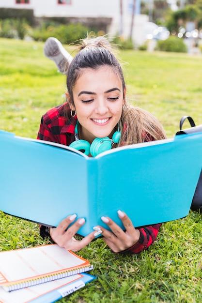 Heureuse adolescente allongée sur la pelouse en lisant le livre Photo gratuit