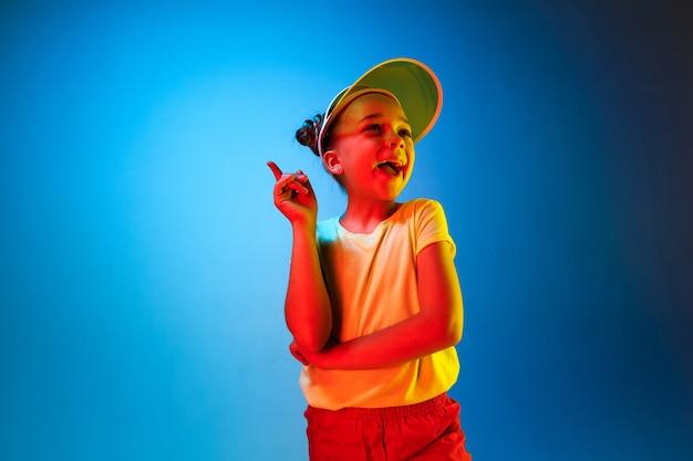 Heureuse Adolescente Debout, Souriant Et Pointant Vers Le Haut Sur L'espace Néon Bleu à La Mode. Beau Portrait Féminin. Jeune Fille Satisfaite Photo gratuit