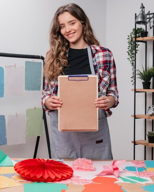 Heureuse artiste féminine séduisante montrant le presse-papiers avec du papier brun ordinaire Photo gratuit