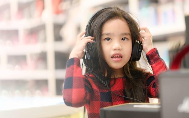 Heureuse asiat étudiante écoutant de la musique avec des écouteurs Photo Premium