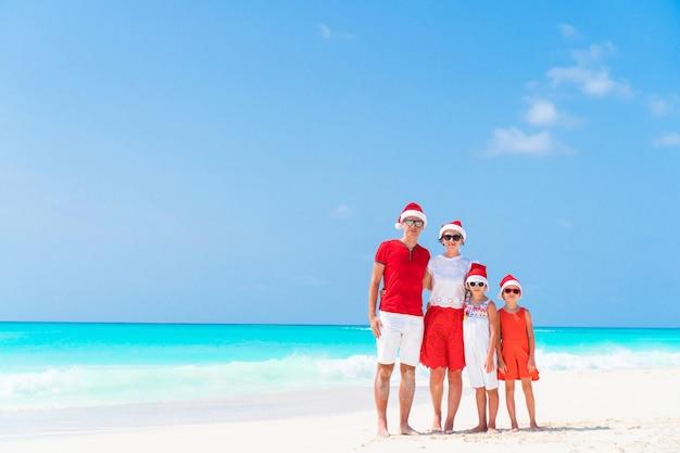 Heureuse belle famille en chapeaux de père noël rouge sur une plage tropicale, célébrant noël Photo Premium