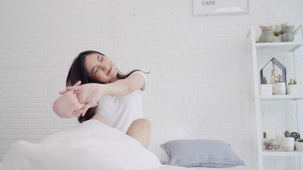 Heureuse belle femme asiatique se réveiller en souriant et en étirant ses bras dans son lit dans la chambre. Photo gratuit