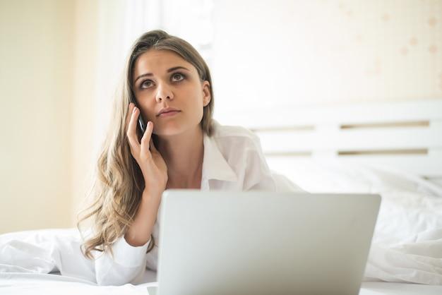 Heureuse belle femme travaillant sur un ordinateur portable sur le lit de la maison Photo gratuit
