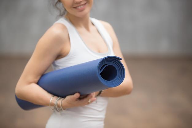 Heureuse belle femme yogi tenant son tapis, gros plan Photo gratuit