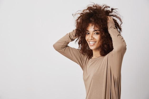 Heureuse Belle Fille Africaine Souriante Touchant Ses Cheveux. Mur Blanc. Photo gratuit