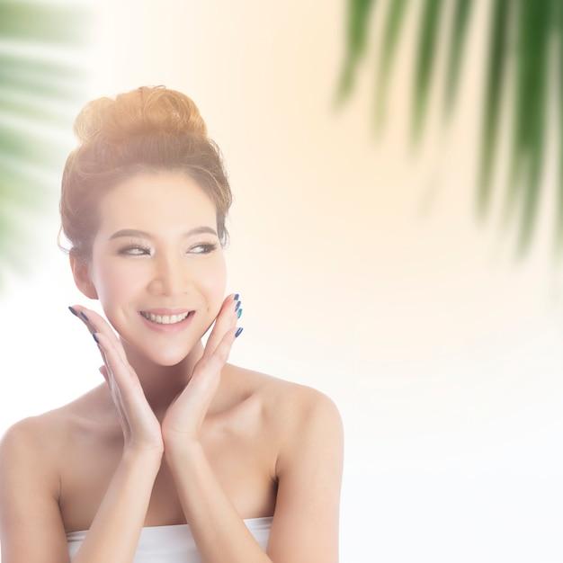 Heureuse belle fille asiatique avec la peau fraîche avec la lumière du soleil Photo Premium