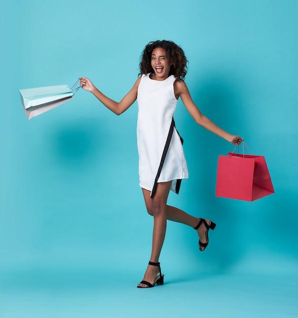 Heureuse Belle Jeune Femme Africaine En Robe Blanche Et Tenant Des Sacs Shopping Sur Bleu Photo Premium