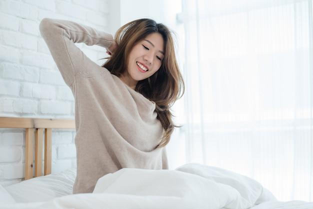 Heureuse belle jeune femme asiatique se réveiller le matin, assise sur le lit, s'étendant dans une chambre confortable Photo gratuit