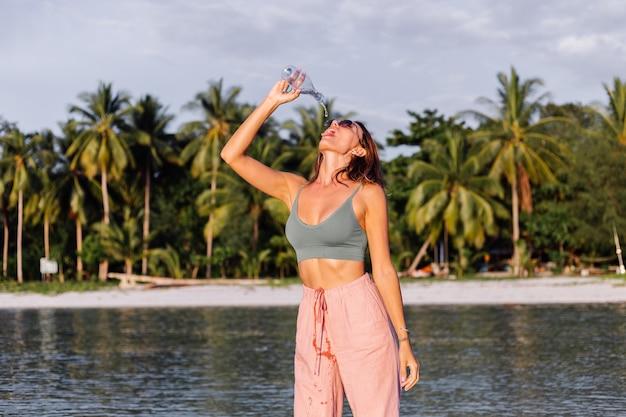 Heureuse Belle Jeune Femme Européenne Avec Une Bouteille D'eau En Plastique Dans Sa Main Sur La Plage Photo gratuit