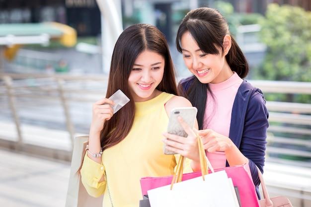 Heureuse belle jeune femme faire du shopping avec smartphone, carte de crédit pour acheter et sac à provisions et téléphone mobile. Photo Premium