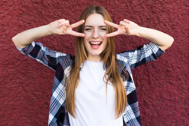 Heureuse belle jeune femme avec le geste de la paix sur fond de mur rouge Photo gratuit