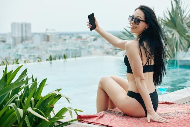 Heureuse Belle Jeune Femme, Passer Du Temps Au Bord De La Piscine à Débordement Et Prendre Selfie Photo Premium