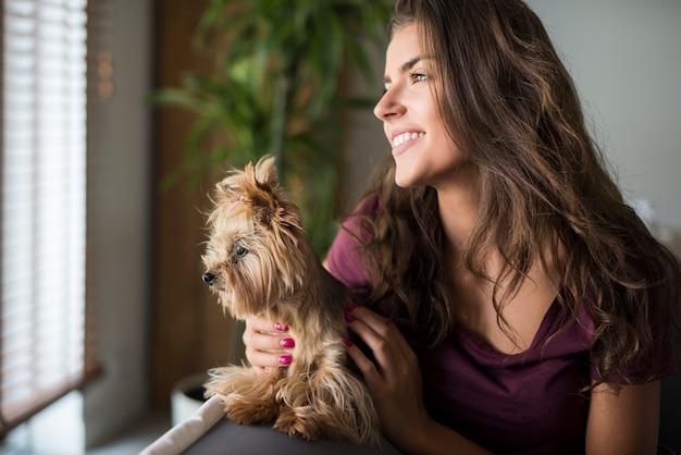 Heureuse Belle Jeune Femme Regardant La Fenêtre Avec Son Chien Photo gratuit