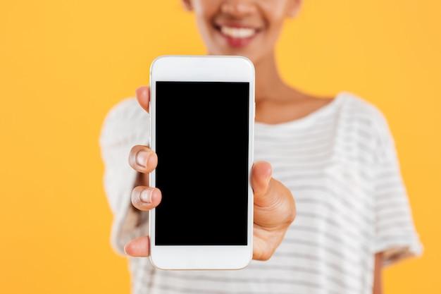 Heureuse Dame Africaine Montrant Le Téléphone Avec écran Blanc Isolé Photo gratuit