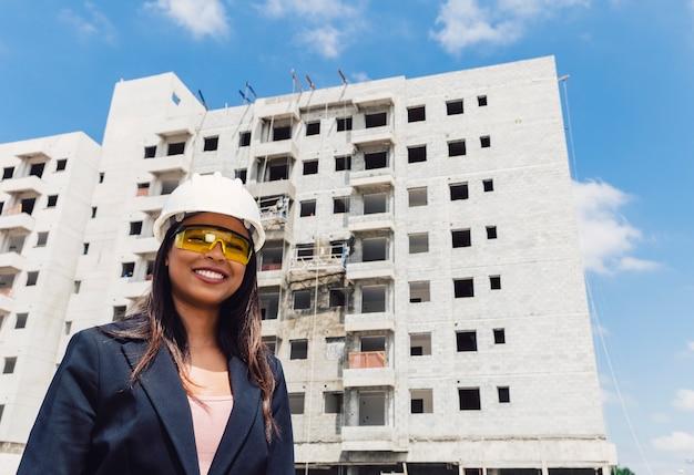 Heureuse dame afro-américaine dans un casque et des lunettes de sécurité près du bâtiment en construction Photo gratuit