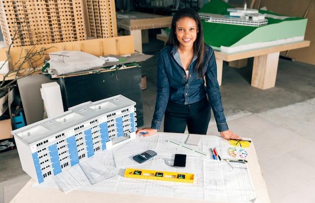 Heureuse dame afro-américaine debout près de modèle de construction sur table Photo gratuit