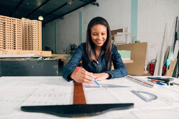 Heureuse dame afro-américaine avec une grande règle et un stylo à la table Photo gratuit