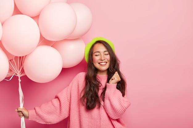 Heureuse Dame Asiatique Brune Heureuse Se Tient Avec Des Ballons, Profite D'une Fête Cool Avec Des Amis, Porte Un Béret Et Un Pull Ample, Célèbre Son Anniversaire Photo gratuit
