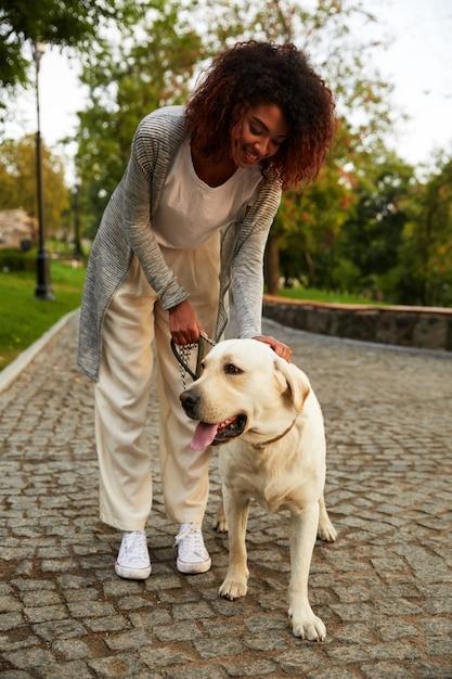 Heureuse Dame étreignant Son Chien Amical Blanc Tout En Marchant Dans Le Parc Photo Premium