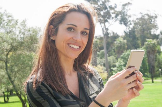 Heureuse dame joyeuse à l'aide d'un smartphone à l'extérieur Photo gratuit