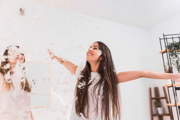 Heureuse deux femmes qui dansent sous la plume blanche qui tombe Photo gratuit