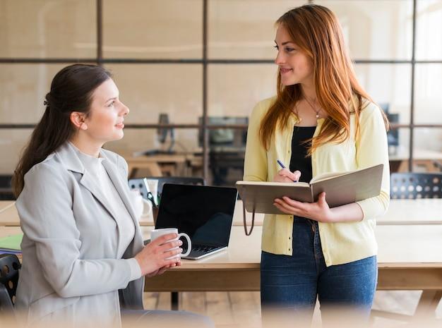 Heureuse deux jolie femme travaillant ensemble au lieu de travail Photo gratuit