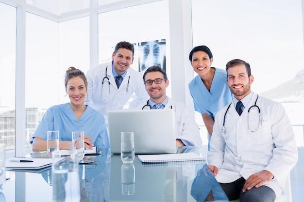 Heureuse équipe médicale utilisant un ordinateur portable ensemble Photo Premium