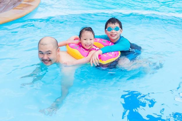 Heureuse famille asiatique jouant ensemble dans la piscine Photo Premium