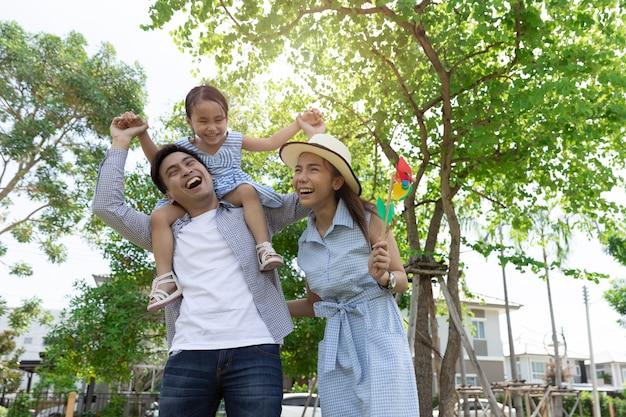 Heureuse famille asiatique. le père a donné sa fille dans un parc à la lumière naturelle du soleil et à la maison. concept de vacances en famille Photo Premium