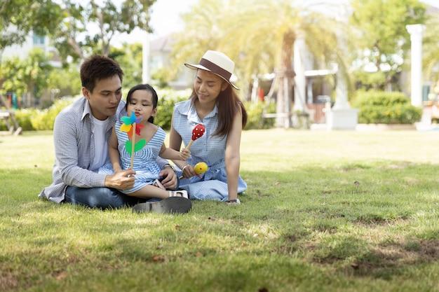 Heureuse famille asiatique. père, mère et fille dans un parc à la lumière naturelle du soleil. concept de vacances en famille. Photo Premium