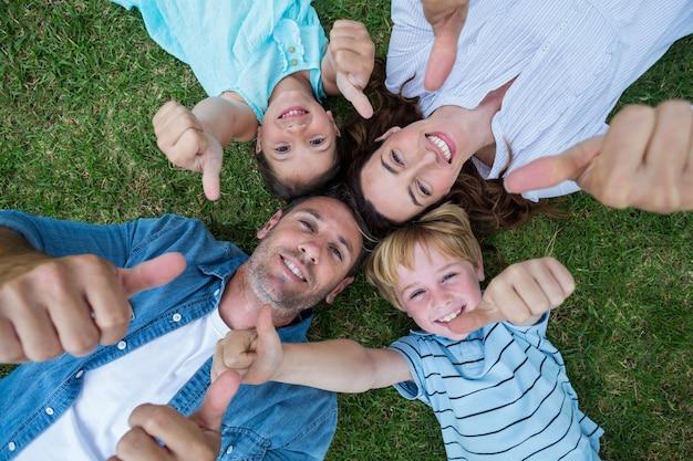 Heureuse famille dans le parc ensemble pouce en l'air par une journée ensoleillée Photo Premium