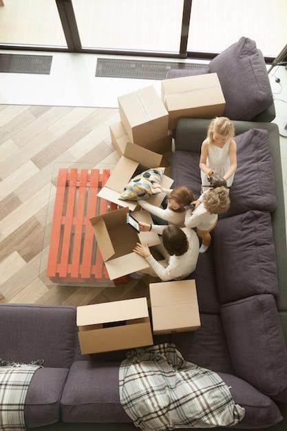 Heureuse famille et enfants, déballage des boîtes de déménagement, vue de dessus Photo gratuit