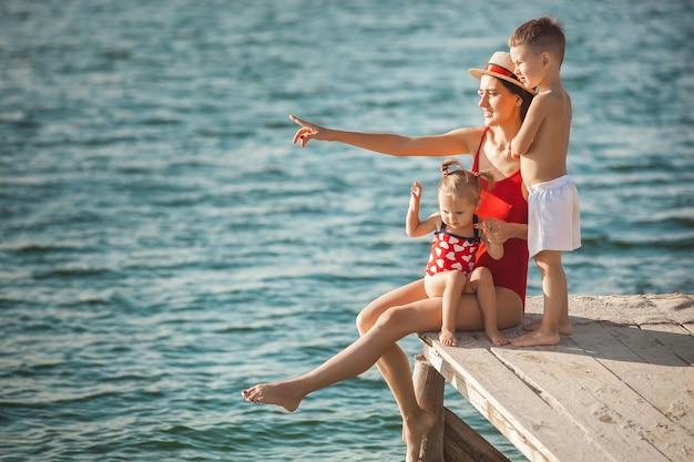 Heureuse Famille Joyeuse à L'embarcadère Près De L'eau S'amuser. Adorables Enfants Jouant Avec Leurs Parents Photo Premium