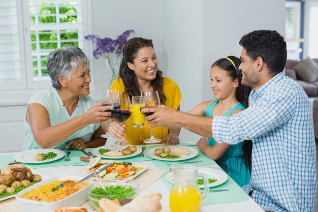 Heureuse Famille De Mutigénération Griller Un Verre De Vin Rouge Tout En Prenant Son Repas Photo Premium