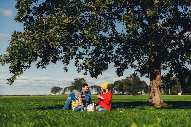 Heureuse famille pique-niquer en automne, s'asseoir sur l'herbe verte, boire du thé chaud, communiquer entre eux Photo Premium