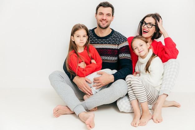 Heureuse famille de quatre membres: une jolie femme brune, son mari et ses deux petites filles assis sur le sol Photo Premium