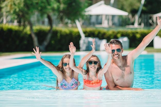 Heureuse famille de quatre personnes dans la piscine en plein air Photo Premium