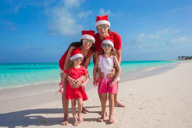 Heureuse famille de quatre personnes sur la plage avec des chapeaux rouges Photo Premium