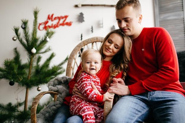 Heureuse famille souriante au studio sur fond de l'arbre de noël avec cadeau Photo gratuit