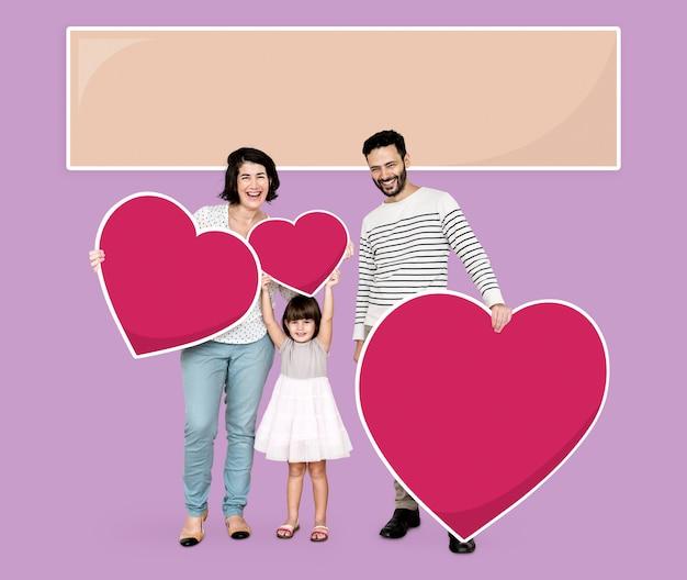 Heureuse famille tenant des icônes de coeur Photo gratuit