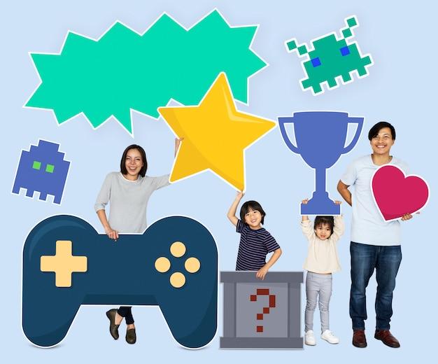 Heureuse famille tenant des icônes de jeu Photo Premium