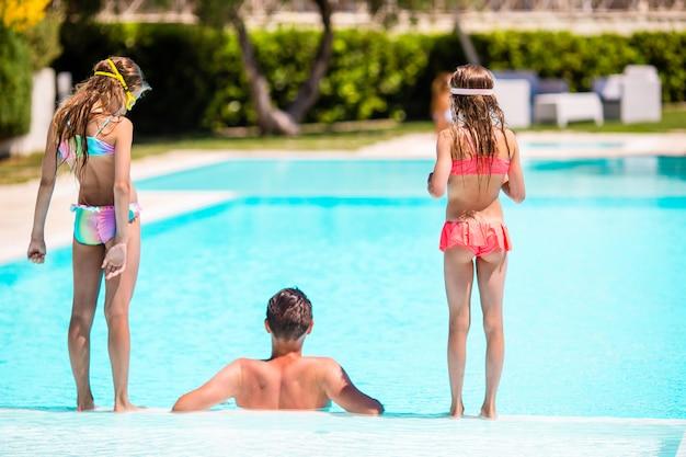 Heureuse famille de trois personnes dans la piscine en plein air Photo Premium