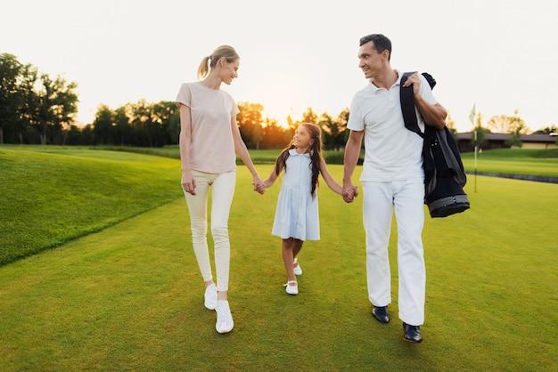 Heureuse famille unie de golfeurs se promène après le match. Photo Premium